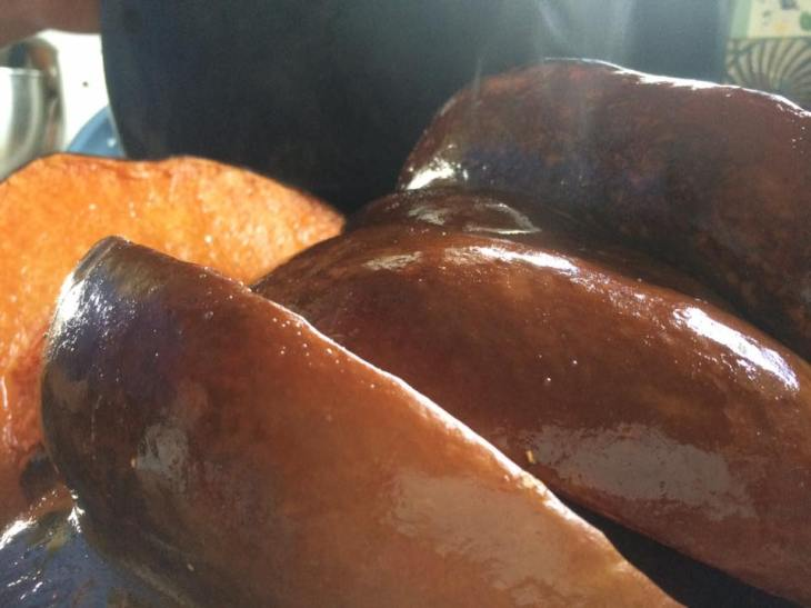 Chunks of roasted pumpkin steam out of the oven. See how the peel has changed color.